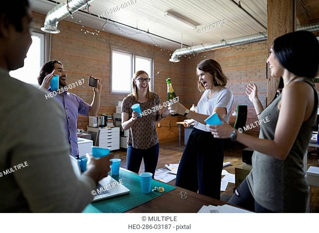 Creative business people celebrating opening bottle of champagne in office