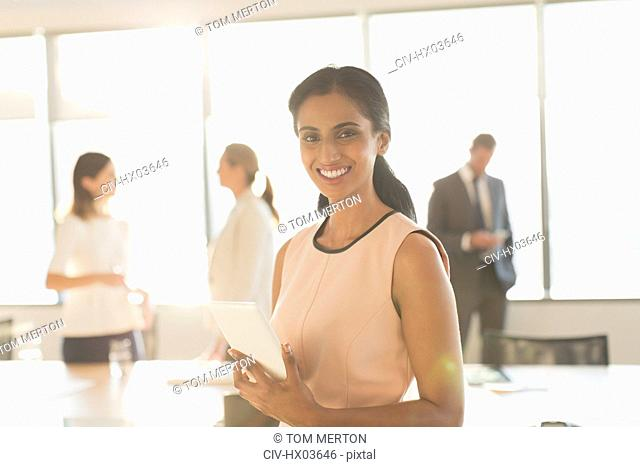 Portrait smiling, confident businesswoman with digital tablet in conference room