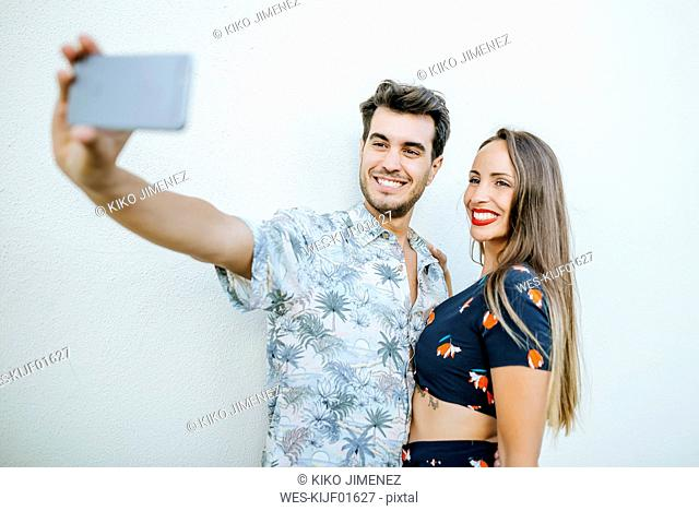 Couple taking a selfie with smartphone in front of white wall