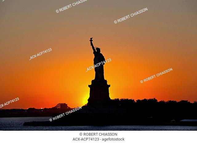Silhouetted Statue of Liberty photographed against the setting sun. Liberty Island, New York, U.S.A