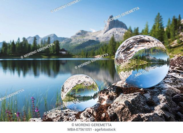 Playing with crystal balls at Lake Federa in summer time, on the background the Becco di Mezzodi, Dolomites, Cortina d'Ampezzo, Belluno, Veneto, Italy