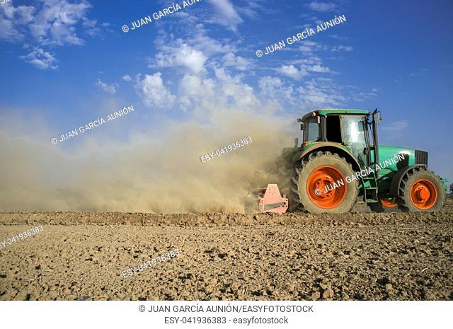 Farm tractor preparing dusty soil affected by drought. Drought and agriculture concept. Spain