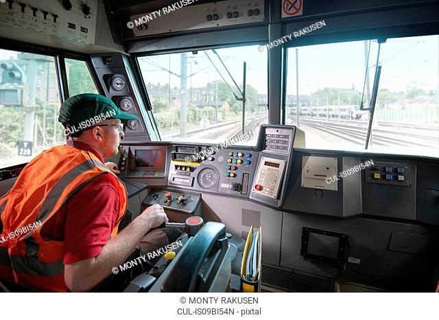 Train driver in stationary locomotive on train tracks