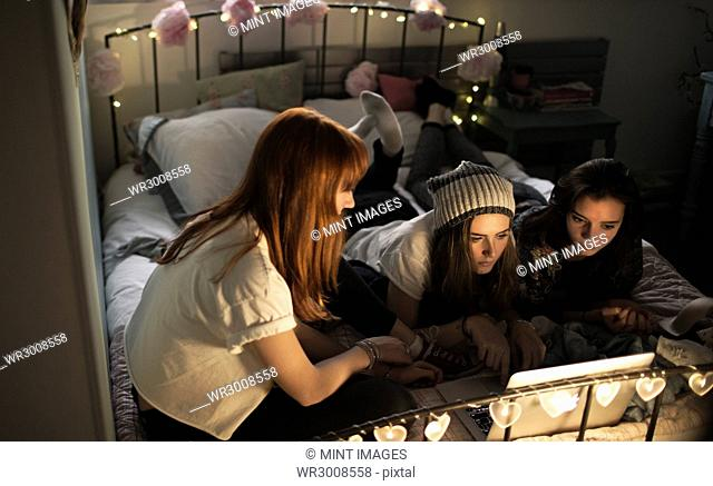 Young women on a bed watching a laptop screen
