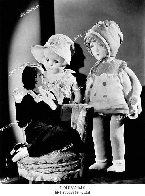 Woman sitting on a chair and looking at two oversized dolls All persons depicted are not longer living and no estate exists Supplier warranties that there will...