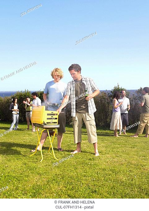 Man tending barbecue with friend