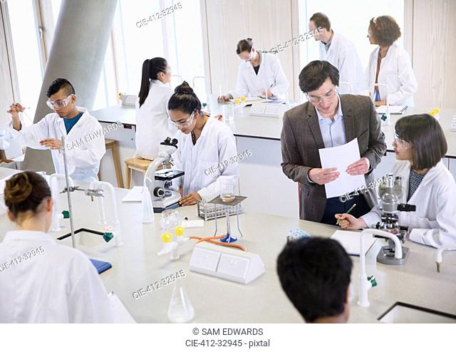 Science professor and college students using microscopes in science laboratory classroom
