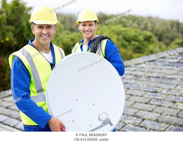 Workers installing satellite dish on roof