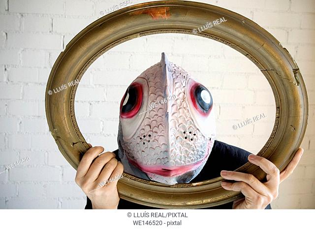 Young woman with a fish mask, behind an antique frame