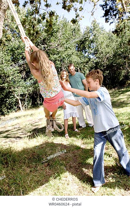 Boy pushing his sister on a rope swing with their parents in the background