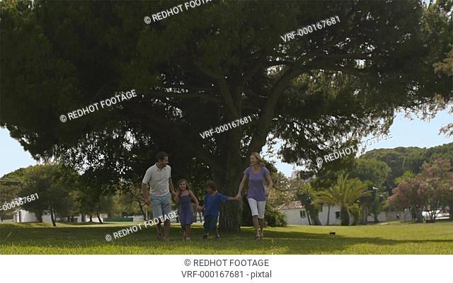 Slow motion low angle tilt up shot of family running in park, Marbella region, Spain