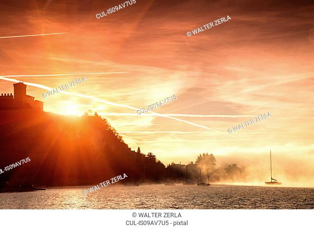Bright sunlight behind cliffs, Lake Maggiore, Piedmont, Lombardy, Italy