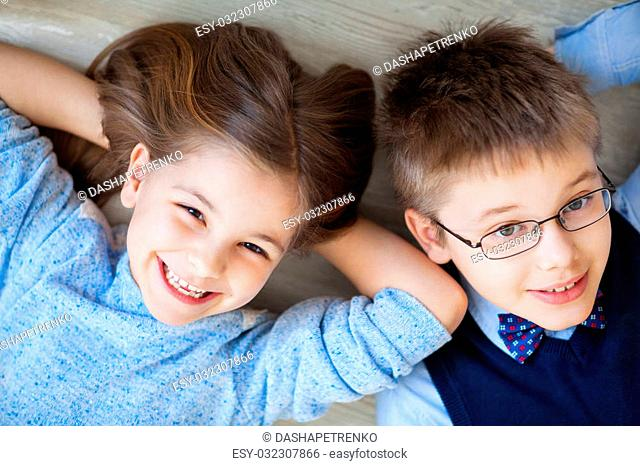 Happy kids are lying together on the floor havinh fun