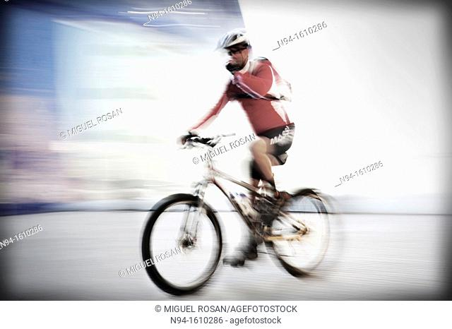 Young man biking through the city