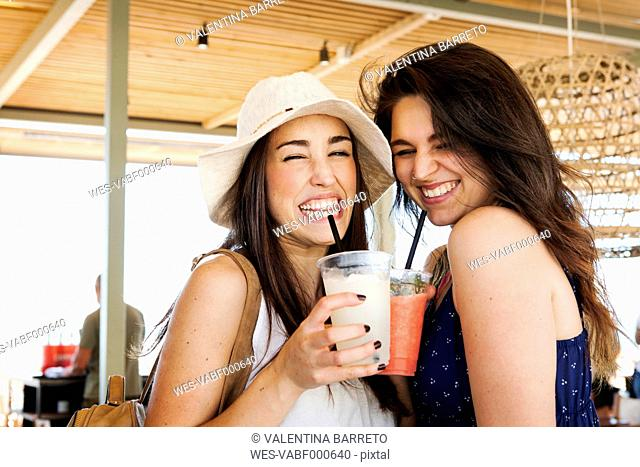 Two young woman drinking cocktails in beach bar