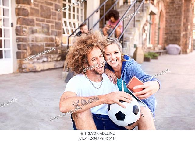 Couple with soccer ball taking selfie with camera phone