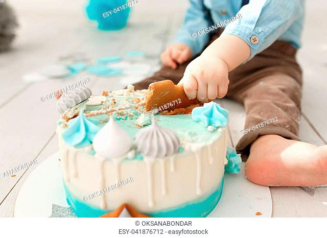 Close up of a caucasian birthday boy legs and arms while he destroys and smashes his cream cake with mint and white icing getting the sticky icing all over her...
