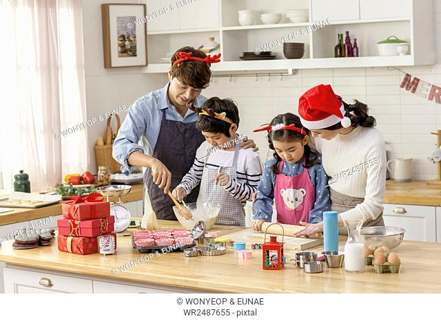 Harmonious family making cookies for Christmas party together looking down in kitchen