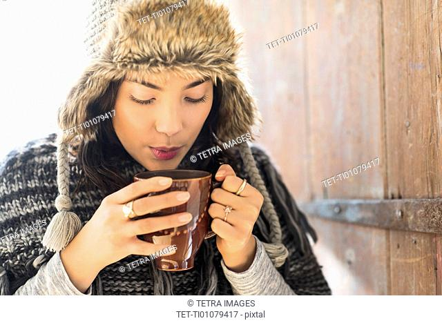 Portrait of young woman wearing warm hat, blowing on cup of drink