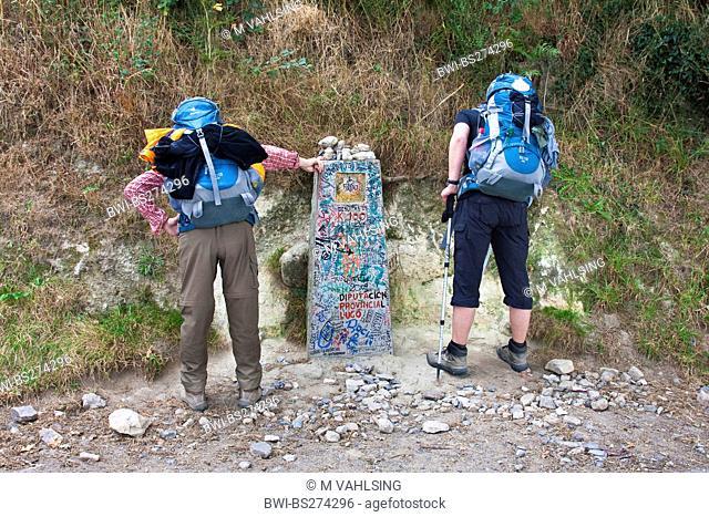 two pilgrim at the kilometre stone 100 at the way from Brea to Morgade, Spain, Galicia, Lugo