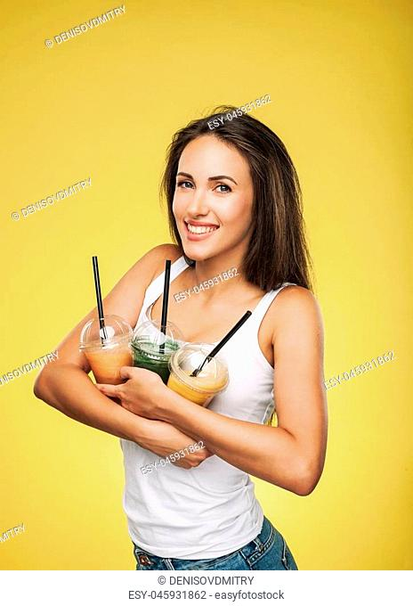 Young attractive brunette woman holding takeaway cups of smoothie. Happy girl posing on yellow background. Healthy eating concept