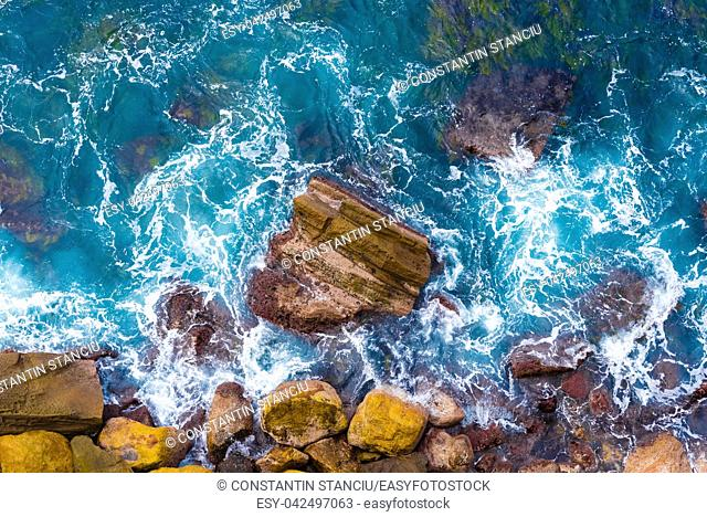 Top aerial view of blue waves crashing on rocky Australian coastline. Summer seascape with birds eye view shot over ocean waves and cliffs