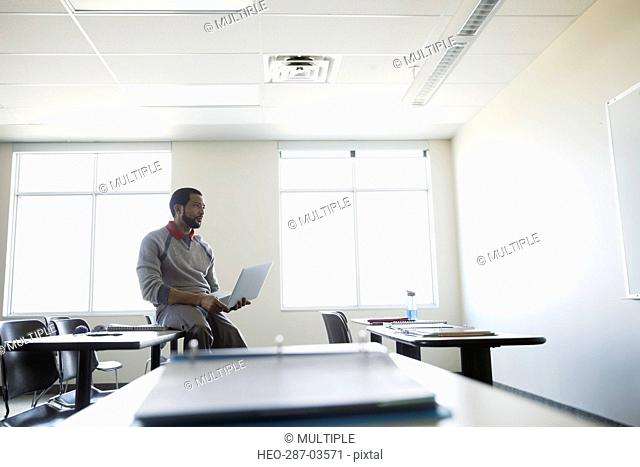 Professor with laptop looking at whiteboard in classroom