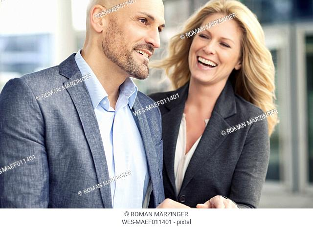 Businessman and happy businesswoman outdoors