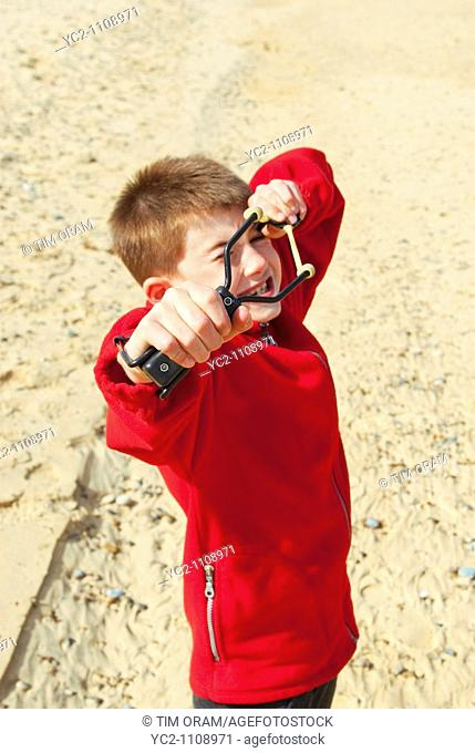 A nine year old boy with his catapult on a uk beach