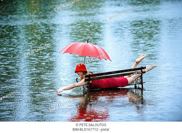 Caucasian woman laying on bench in flood