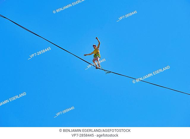 young man balancing on highline slackline enjoying the freedom of blue sky in Bavarian alps, near mountain Blankenstein, south of Germany