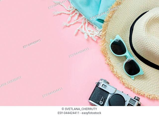 Straw beach sun-hat and sun glasses on punchy pink with space for text. Female outfit for beach. Summer concept