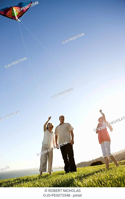 Grandparents and granddaughter flying kite on grass overlooking ocean