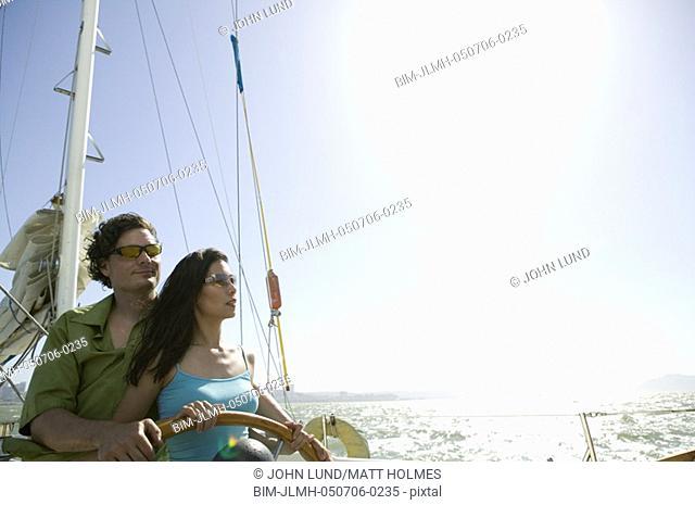 Couple steering sailboat in sunlight