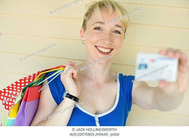 Portrait of a mid adult woman holding shopping bags and showing a credit card