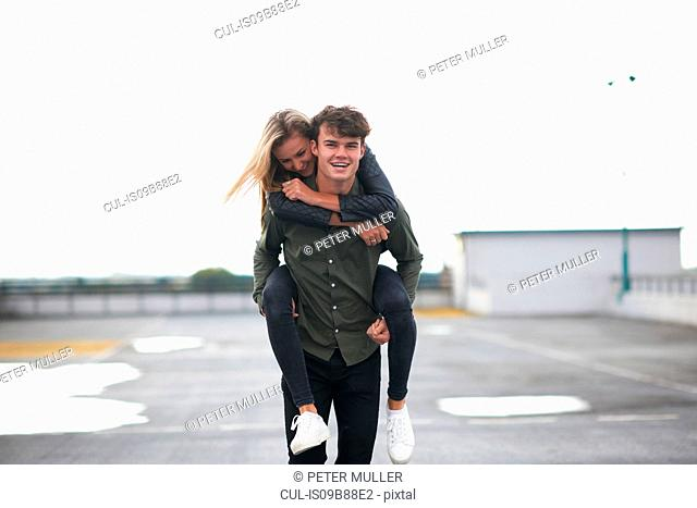 Young man giving girlfriend a piggyback across car park