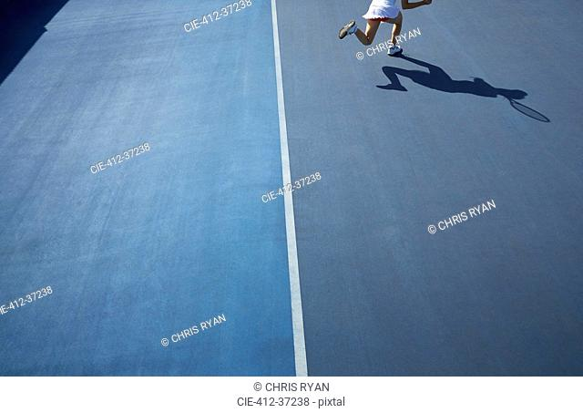Shadow of female tennis player running on sunny blue tennis court