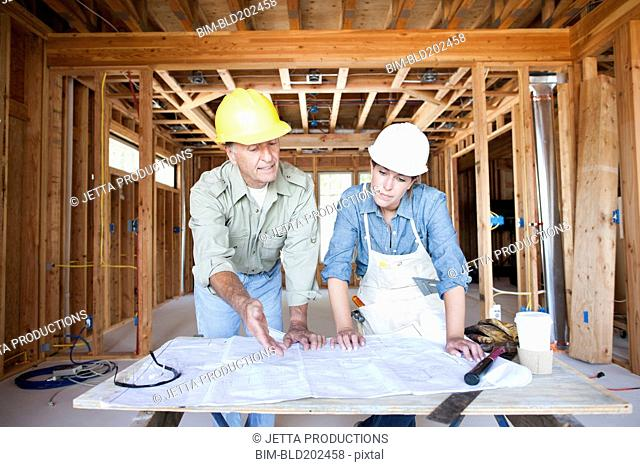 Caucasian construction workers looking at blueprints in unfinished room
