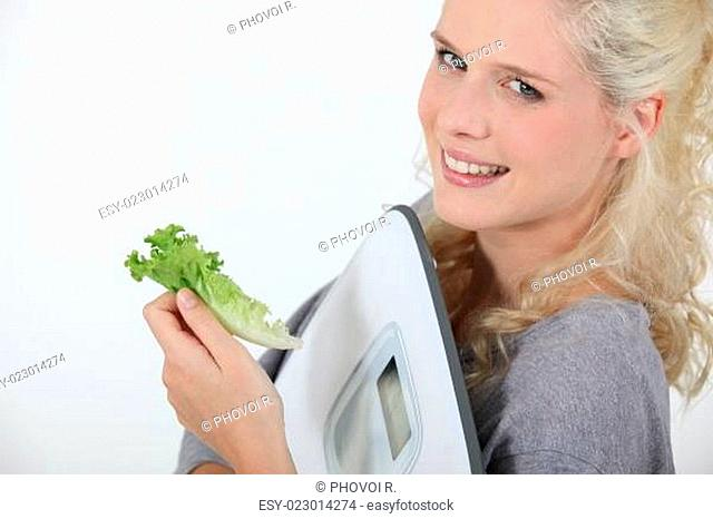 portrait of angel-faced blonde carrying scales with salad leaf in hand