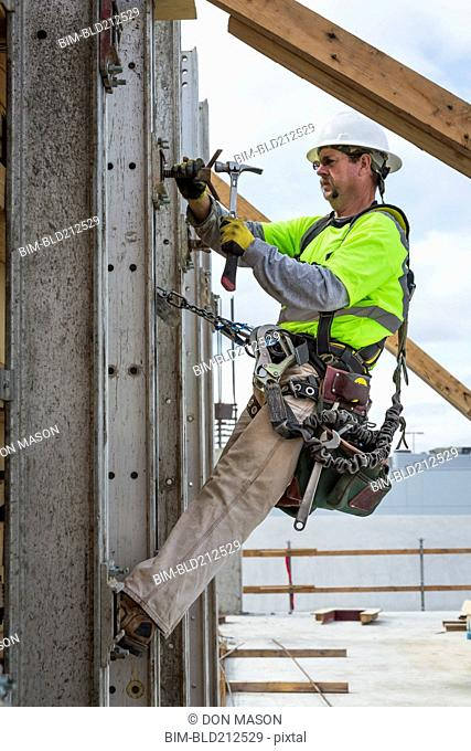 Caucasian worker hammering nails at construction site