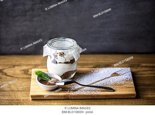 Chocolate parfait dessert with spoon and powdered sugar fork outline