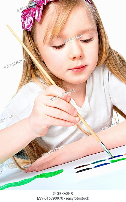 pretty little girl paints with a brush on paper