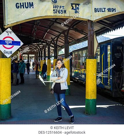 A woman standing at a station for the Darjeeling Toy Train, The Darjeeling Himalayan Railway; Ghoom, West Bengal, India