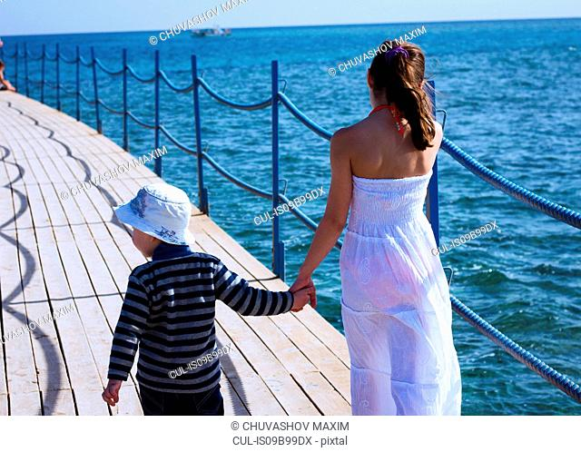 Rear view of girl strolling along sea pier hand in hand with brother