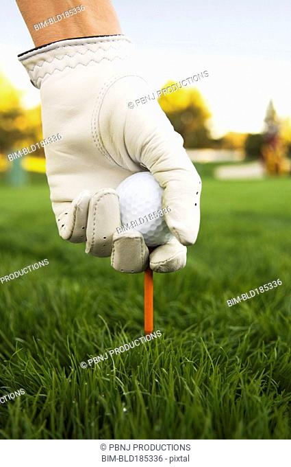Mixed race woman placing ball on tee at golf course