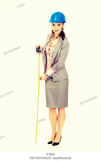 Engineer woman in suit holding tape measure in hand