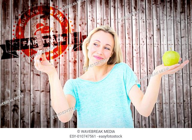 Composite image of smiling blonde holding bar of chocolate and apple