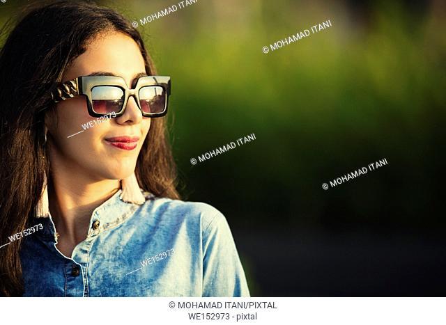 Beautiful young woman wearing sunglasses looking away
