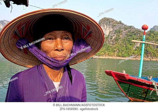 Vietnam, Halong Bay, Old woman in purple in fishing village