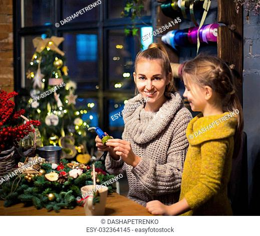Mother and daughter decorating coniferous wreath. Christmas celebration concept
